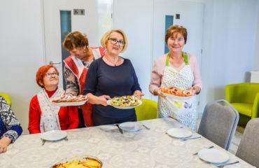 Zdjęcie główne przedstawia uczestników Klubu SENIOR+ podczas warsztatów kulinarnych.
