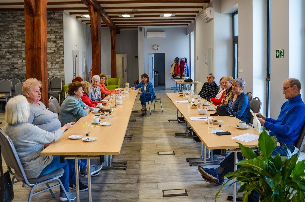 Zdjęcie główne przedstawia seniorów podczas spotkania pod nazwą Kawiarenka Seniora